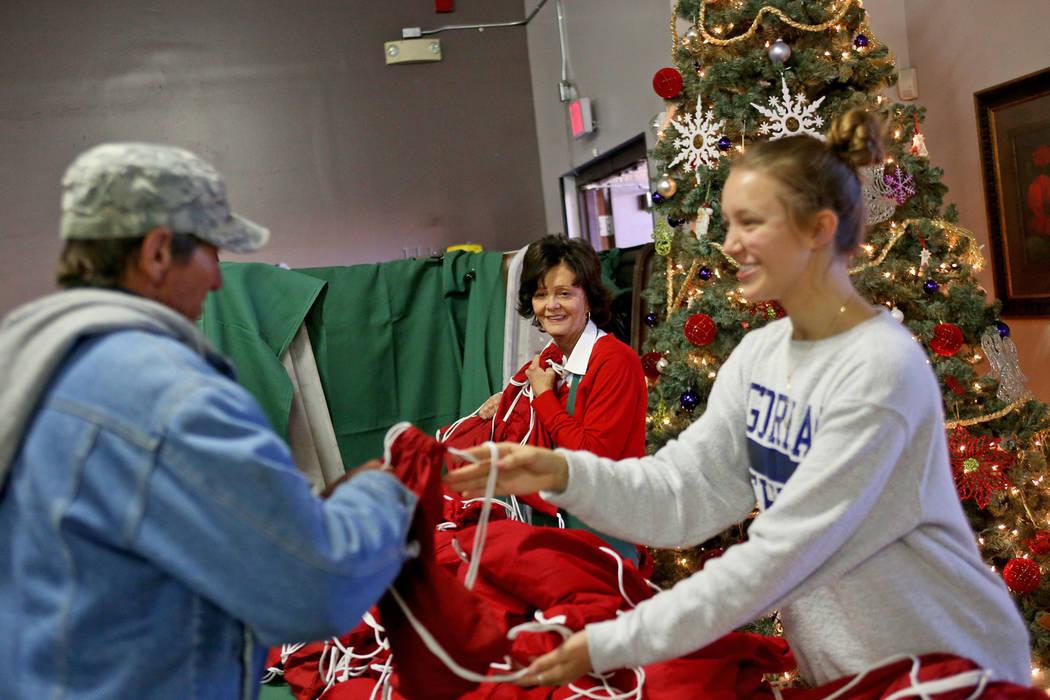 Victoria Fertitta ve como Caroline Nielson, de 17 años, le entrega una bolsa de regalo con artículos de tocador, agua y calcetines a un invitado en la comida de Navidad patrocinada por la Fundac ...