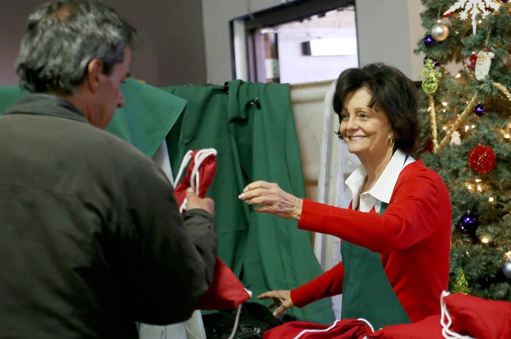 Victoria Fertitta le entrega una bolsa de regalo de artículos de tocador, agua y calcetines a un invitado en la cena de Navidad patrocinada por la Fundación Frank y Victoria Fertitta, en Catholi ...