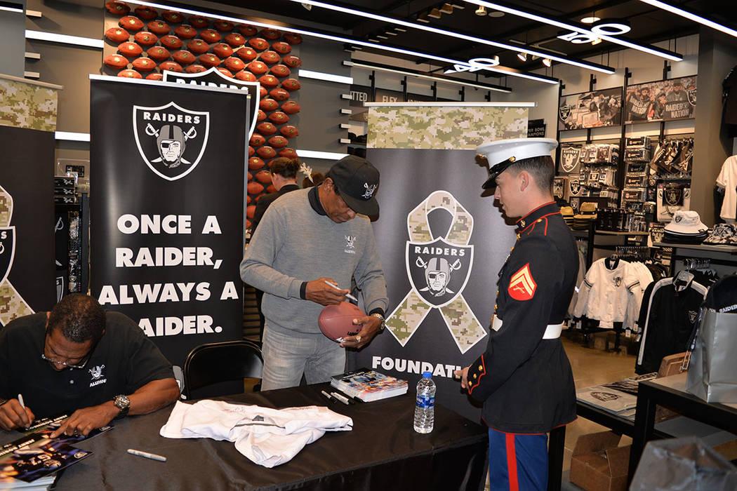 Los ex-jugadores de los Raiders, Cliff Branch, receptor abierto y Jerry Robinson, linebaker, saludaron y firmaron autógrafos para algunos aficionados, durante la colecta de juguetes para niños, ...