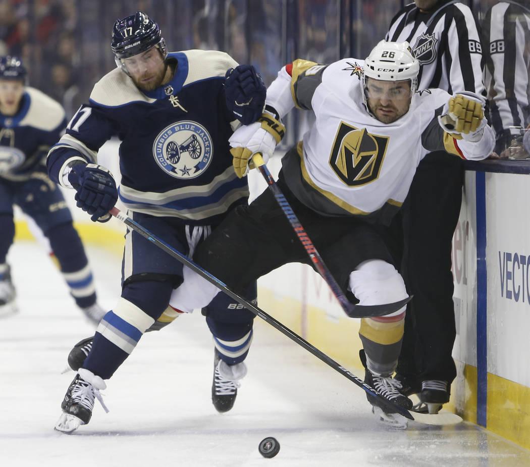 Brandon Dubinsky, de los Columbus Blue Jackets, a la izquierda, y Paul Stastny, de los Golden Knights de Las Vegas, persiguen el disco durante el primer período de un juego de hockey de la NHL el ...
