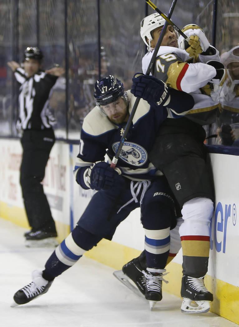 Brandon Dubinsky, de Columbus Blue Jackets, a la izquierda, verifica a Ryan Reaves de los Golden Knights de Las Vegas durante el primer período de un juego de hockey de la NHL el lunes 17 de dici ...