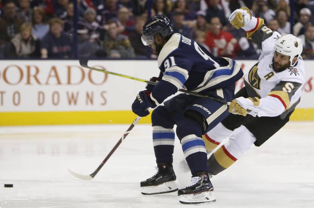 Anthony Duclair de Columbus Blue Jackets, a la izquierda, y Deryk Engelland de los Golden Knights de Vegas se enfrentan durante el segundo período de un juego de hockey de la NHL el lunes 17 de d ...