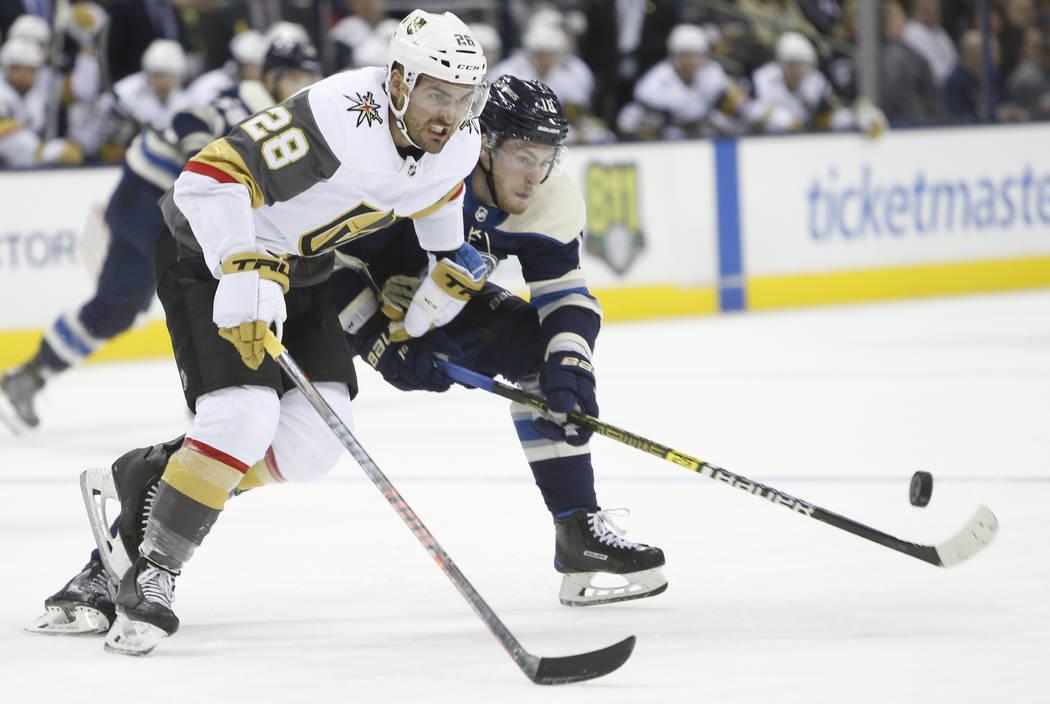 William Carrier de los Vegas Golden Knights, a la izquierda, y Pierre-Luc Dubois, de los Columbus Blue Jackets, persiguen el disco durante el segundo período de un juego de hockey de la NHL el lu ...