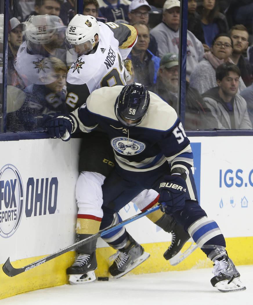 David Savard de Columbus Blue Jackets, a la derecha, controla a Tomas Nosek, de la República Checa, de los Golden Knights de Las Vegas, durante el tercer período de un juego de hockey de la NHL ...
