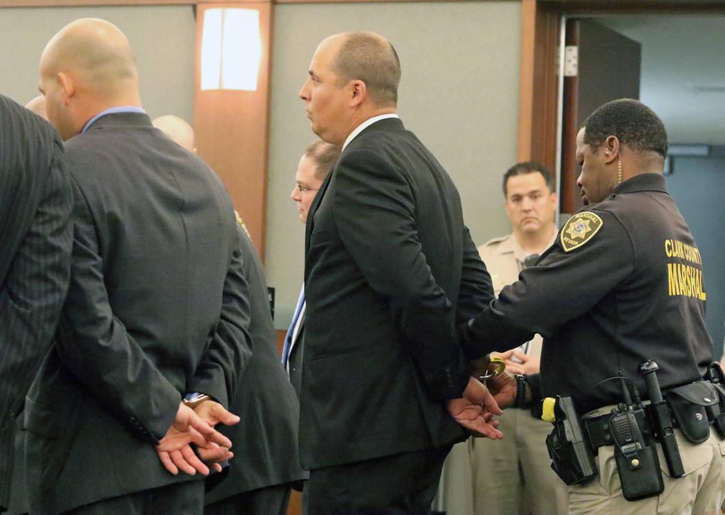Un agente esposa a Jeffrey Martin, quien se encuentra junto Mark Branco esposado, a la izquierda, en la sala de audiencias de la jueza Valerie Adair en el Centro de Justicia Regional, el martes 12 ...
