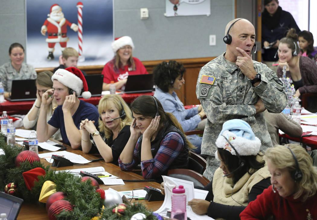ARCHIVO - En esta foto de archivo del 24 de diciembre de 2014, el Jefe de Estado Mayor del NORAD, el Mayor General Charles D. Luckey, recibe una llamada mientras se ofrece como voluntario en el ce ...
