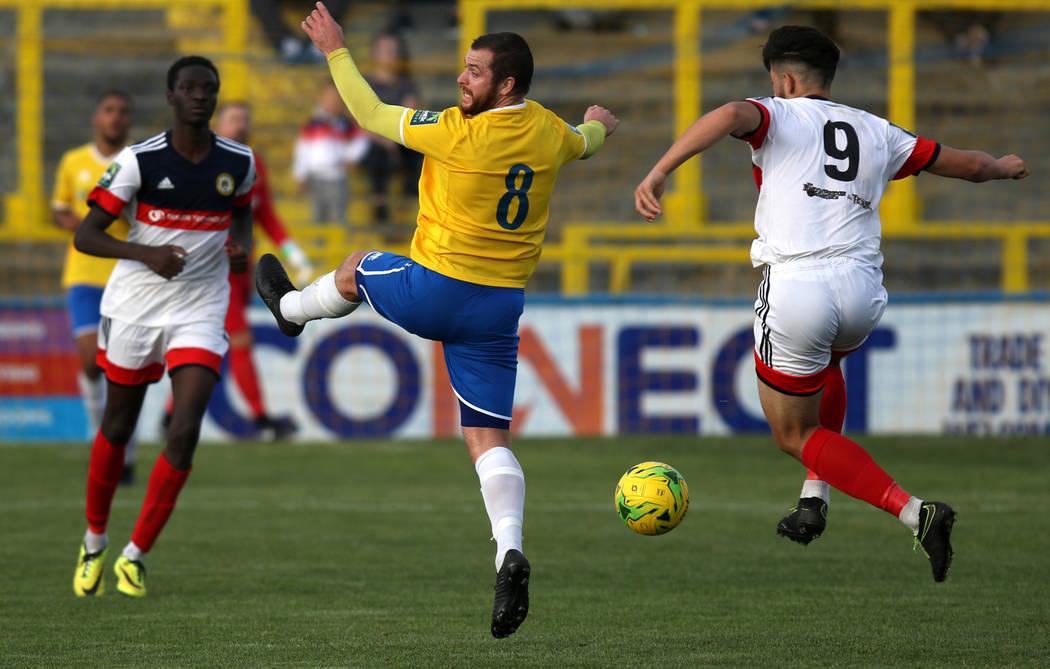El alero de Cray Wanderers, Malik Solebo, izquierda, se mantiene listo mientras el delantero Freddie Parker (9) mueve el balón de fútbol hacia el mediocampista de Canvey Island Gulls, Sam Collin ...