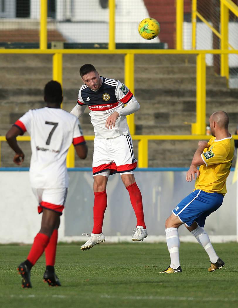 El defensor Jay Leader (4) de Cray Wanderers, centro, encabeza el balón de fútbol cuando Sean Roberts (7) se mueve contra los Gulls de Canvey Island en Canvey Island, Essex, Inglaterra, el sába ...