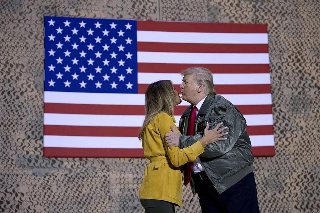 El presidente Donald Trump besa a la primera dama Melania Trump durante un mitin en la Base Aérea Al Asad, Irak, el miércoles 26 de diciembre de 2018. El presidente Donald Trump, quien está de ...