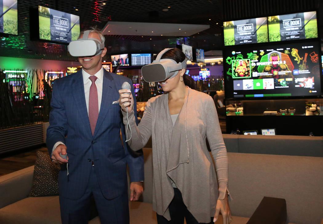 Christian Stuart, a la izquierda, vicepresidente ejecutivo de Caesars Entertainment, Gaming and Interactive Entertainment, y Jennifer Forkish, vicepresidenta de comunicaciones, juegan Xbox one en ...