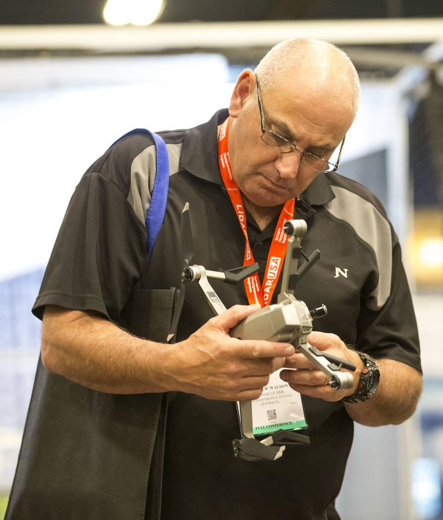 El participante Matthew Waldon de Australia inspecciona un dron DJI Mavic en exhibición en el stand de Drone Nerds durante la tercera exposición anual de UAV comercial en Westgate en Las Vegas e ...