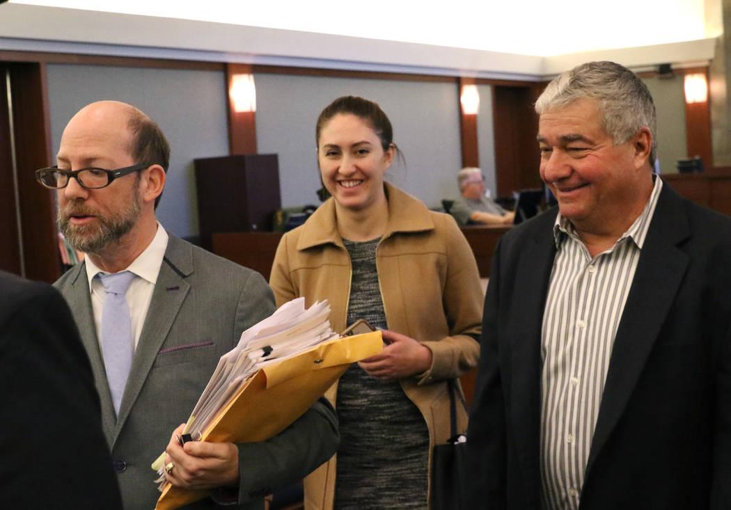 Henderson Constable Earl Mitchell, a la derecha, abandona el tribunal con sus abogados, Dayvid Figler, a la izquierda, y Alanna Bondy, después de su primera apariencia ante el Centro Regional de ...