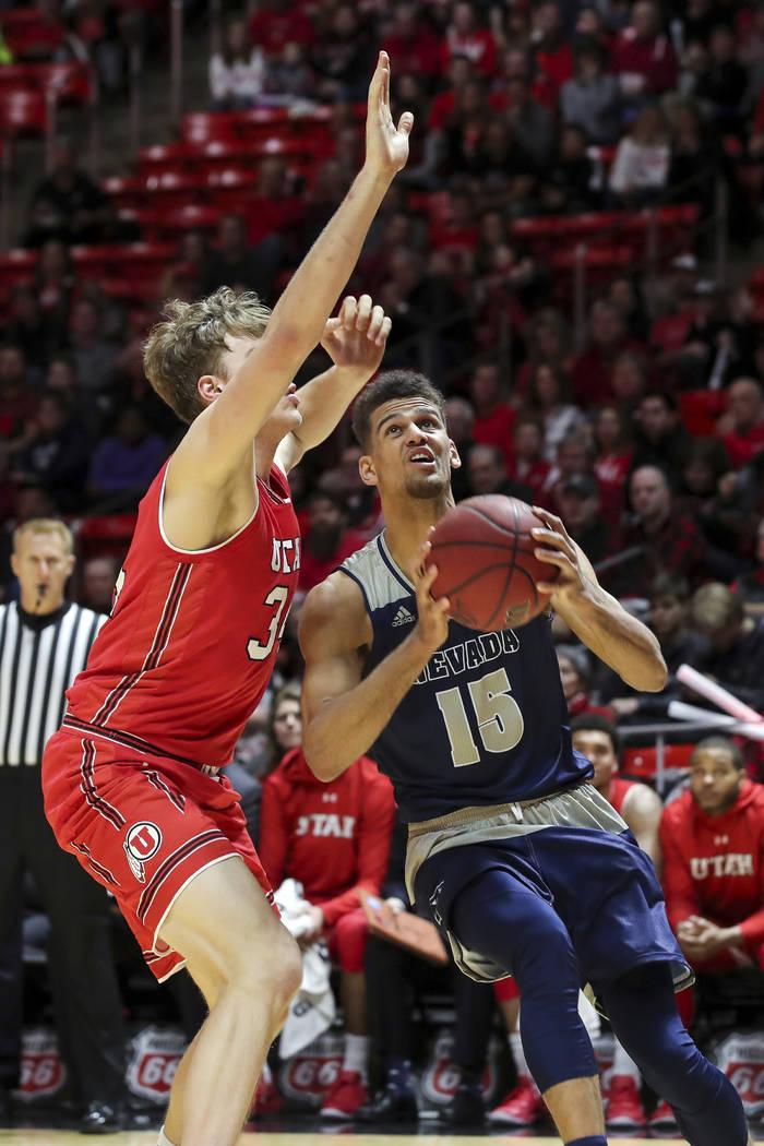 El delantero de Nevada Trey Porter (15) busca disparar el balón al centro de Utah Jayce Johnson (34) durante la primera mitad de un juego de Básquetbol universitario de la NCAA, el sábado 29 de ...
