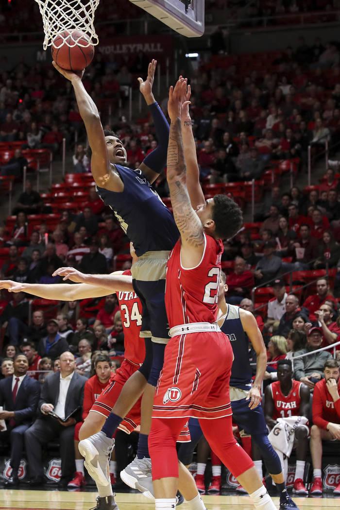 El delantero de Nevada Jordan Brown (21) dispara el balón sobre el delantero de Utah Timmy Allen (20) durante la primera mitad de un partido de Básquetbol universitario de la NCAA, el sábado 29 ...