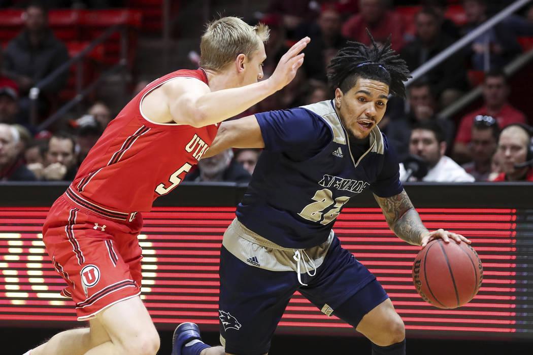 El guardia Jazz Johnson (22) de Nevada dribla el balón mientras está siendo vigilado por el guardia Parker Van Dyke (5) de Utah durante la primera mitad de un partido de Básquetbol universitari ...