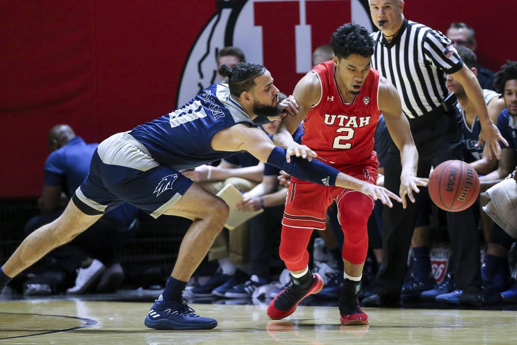 El delantero de Nevada Cody Martin (11) intenta robarle el balón al escolta de Utah Sedrick Barefield (2) durante la primera mitad de un partido de Básquetbol universitario de la NCAA, el sábad ...