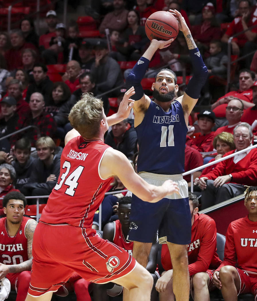 El delantero de Nevada Cody Martin (11) dispara el balón sobre el centro de Utah Jayce Johnson (34) durante la primera mitad de un partido de Básquetbol universitario de la NCAA, el sábado 29 d ...