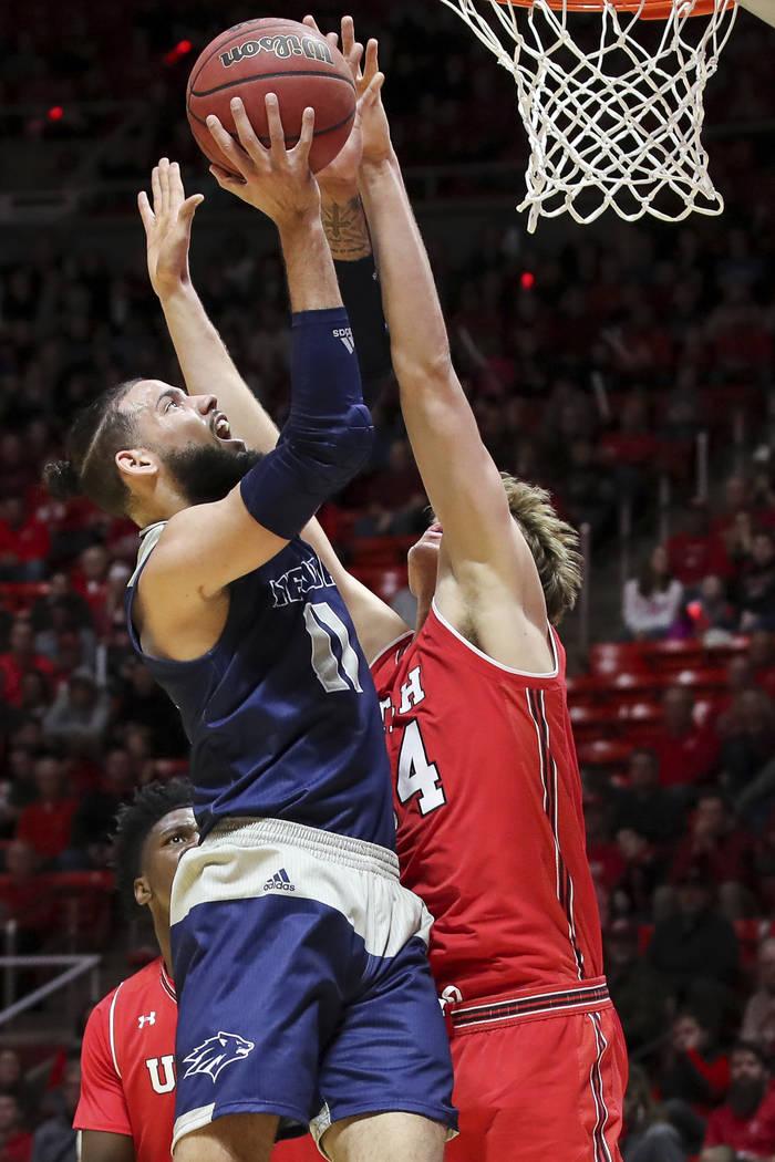 El centro de Utah Jayce Johnson (34) bloquea el tiro del delantero de Nevada Cody Martin (11) durante la primera mitad de un partido de baloncesto universitario de la NCAA, el sábado 29 de diciem ...