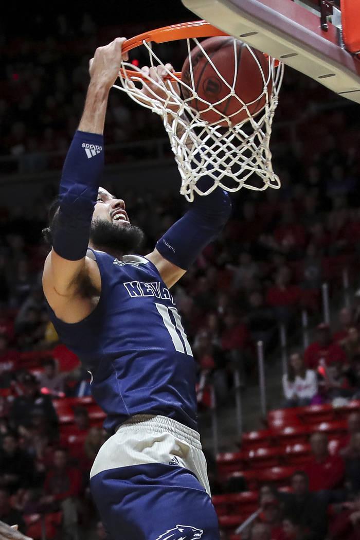 El delantero de Nevada Cody Martin (11) clava el balón contra Utah durante la primera mitad de un partido de básquetbol universitario de la NCAA, el sábado 29 de diciembre de 2018, en Salt Lake ...