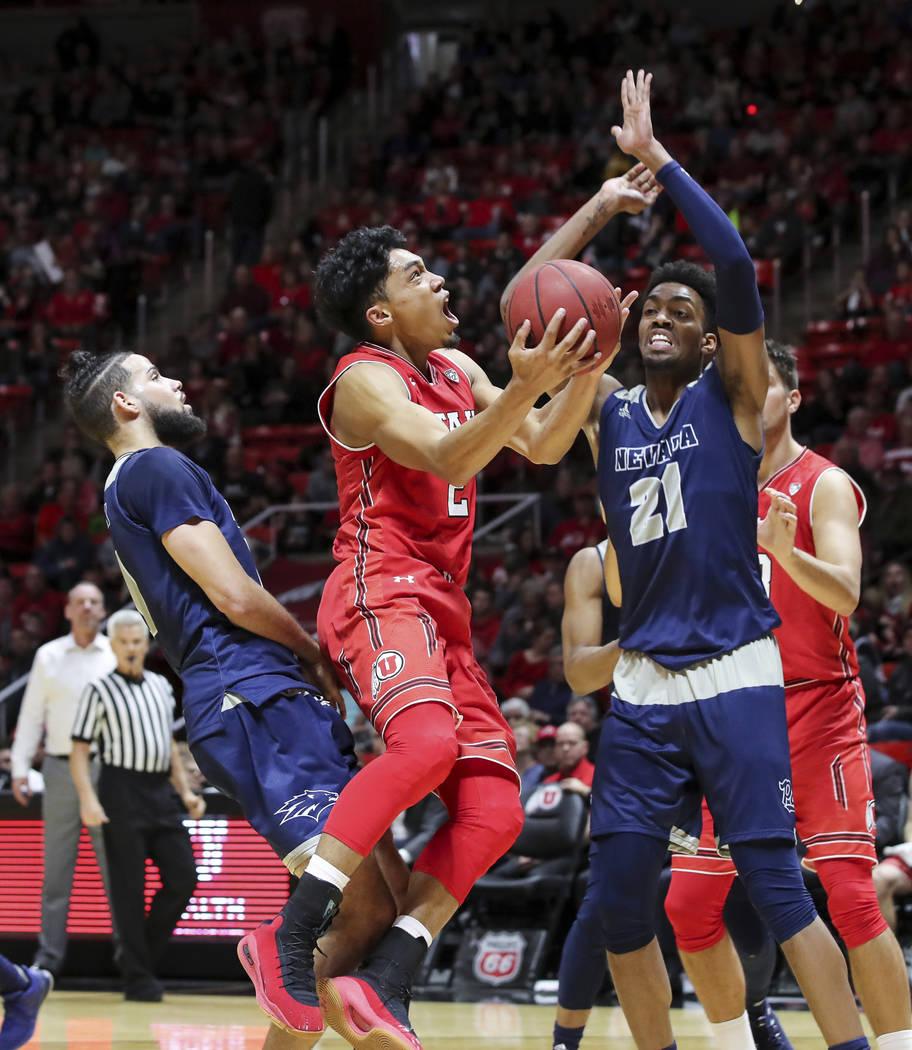 El escolta de Utah, Sedrick Barefield (2), dispara el balón entre los delanteros de Nevada Caleb Martin (10) y Jordan Brown (21) durante la segunda mitad de un partido de básquetbol universitari ...