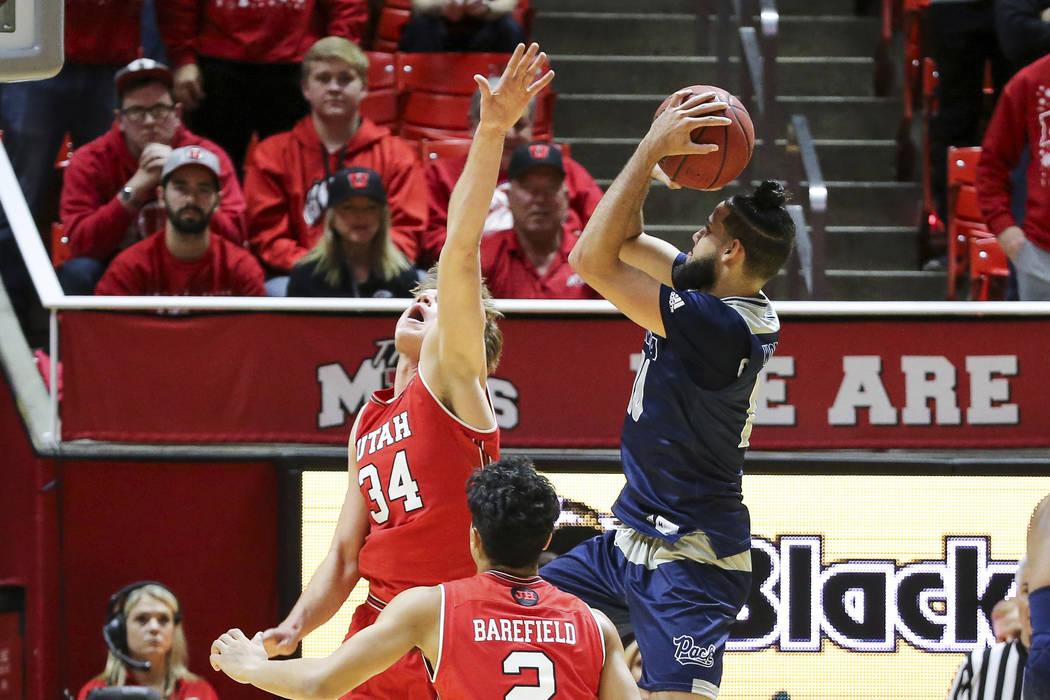 El delantero de Nevada Caleb Martin (10) dispara el balón sobre el centro de Utah Jayce Johnson (34) durante la segunda mitad de un partido de baloncesto universitario de la NCAA, el sábado 29 d ...