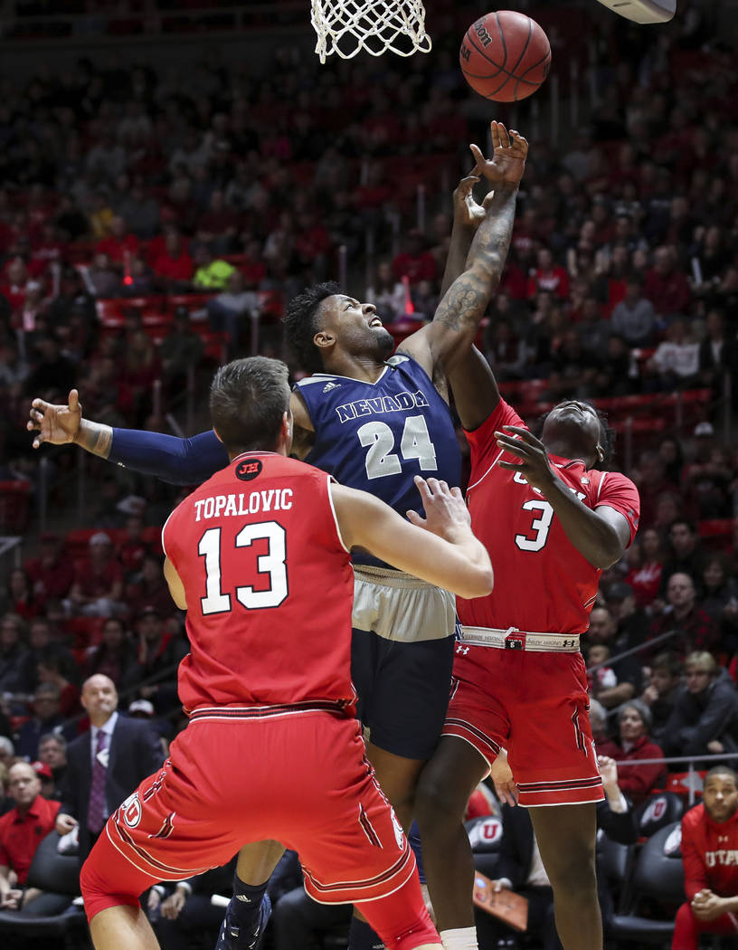 El delantero de Nevada Jordan Caroline (24) y el delantero de Utah Donnie Tillman (3) luchan por un rebote durante la primera mitad de un partido de baloncesto universitario de la NCAA, el sábado ...