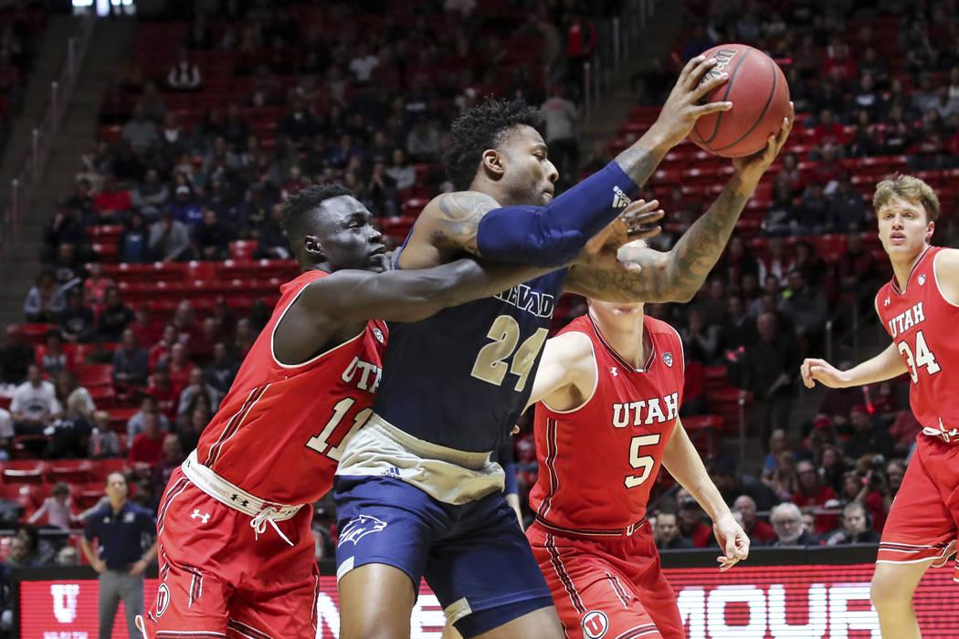 El delantero de Utah Both Gach (11) intenta robarle el balón al delantero de Nevada Jordan Caroline (24) durante la primera mitad de un partido de baloncesto universitario de la NCAA, el sábado ...