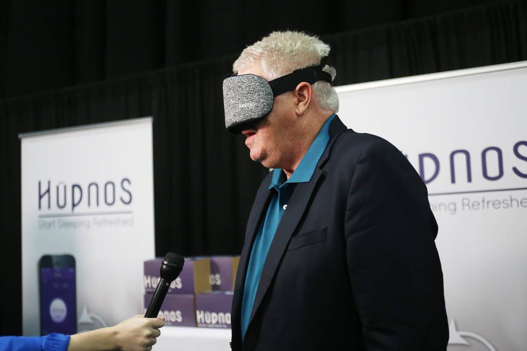 Curtis Ray, fundador de HYpnos, habla a los medios de comunicación mientras usa el dispositivo que es una máscara de autoaprendizaje para reducir ronquidos en el evento CES Unveiled para los med ...