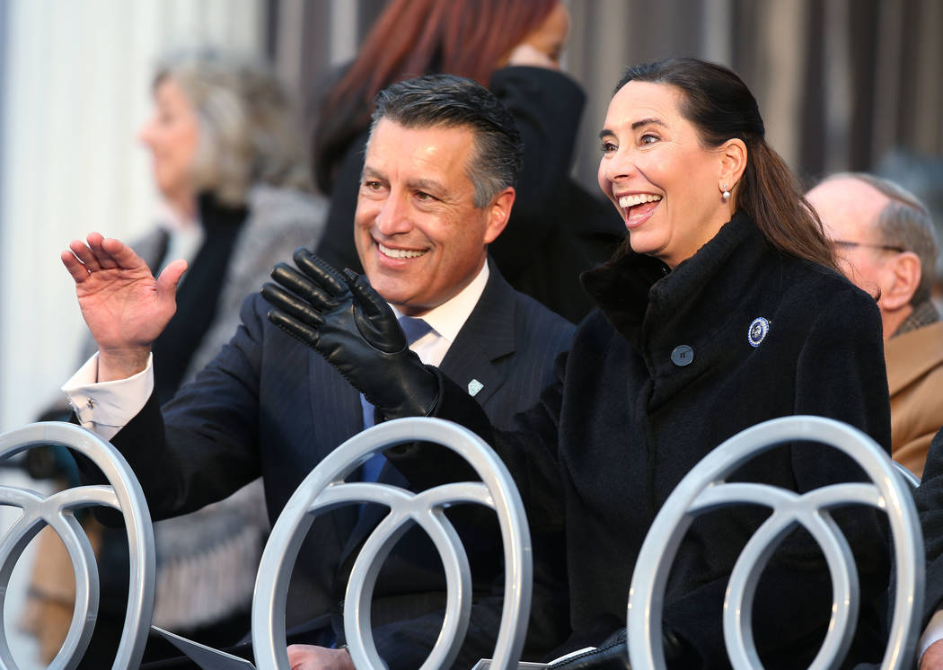 El ex gobernador Brian Sandoval y su esposa Lauralyn saludan a los miembros de la multitud antes de la inauguración en el Capitolio, en Carson City, Nevada, el lunes 7 de enero de 2019. (Cathleen ...
