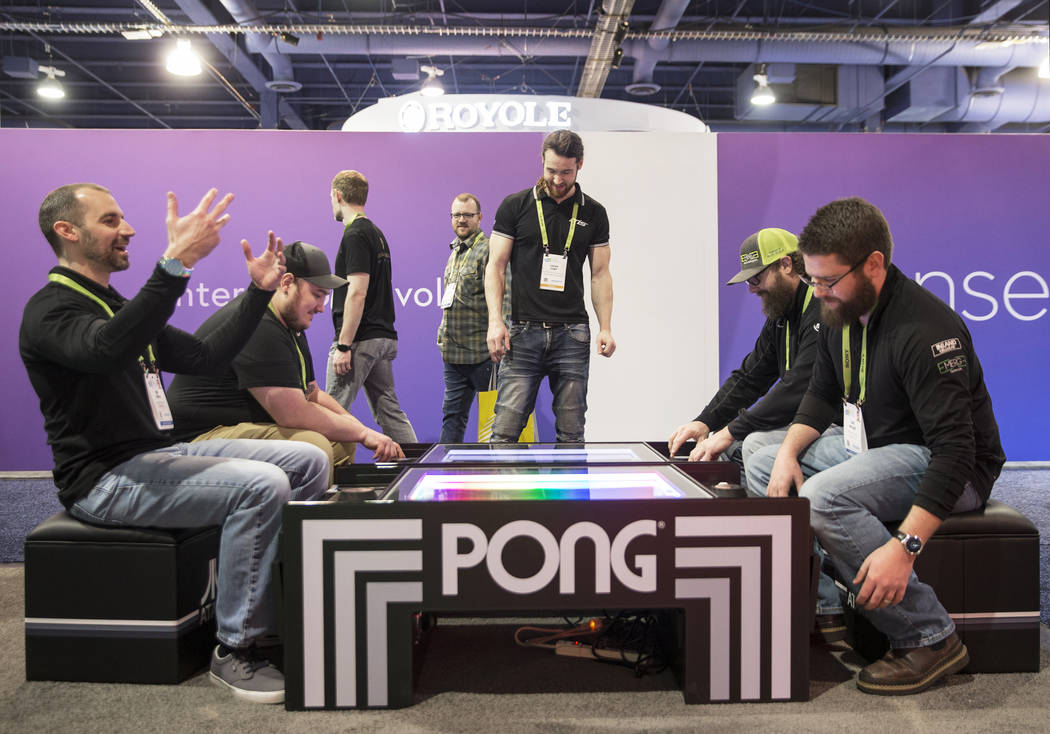 Nik Birge, a la izquierda, celebra después de vencer a Joe Miller en un juego de Pong durante el primer día del CES 2019 el martes 8 de enero de 2019, en el Centro de Convenciones de Las Vegas, ...