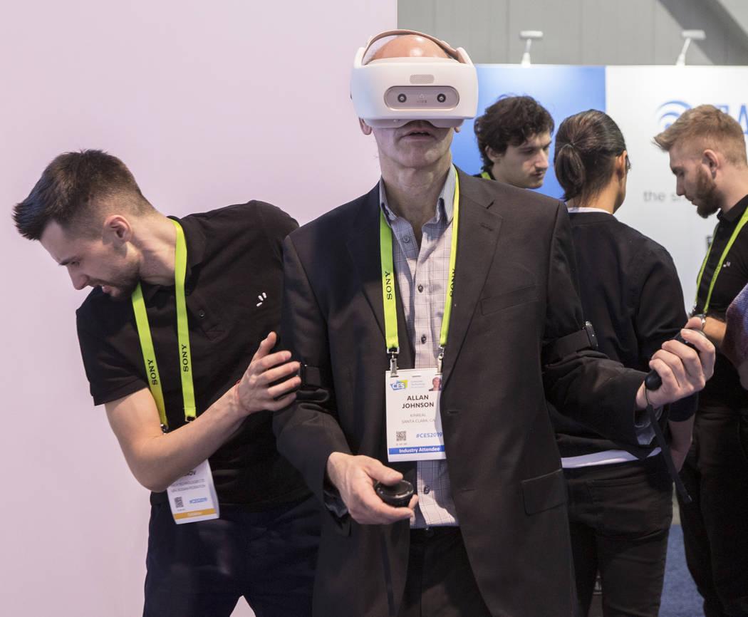 Allan Johnson, en medio, explora un simulador de realidad virtual de Finch Technologies durante el primer día del CES 2019 el martes 8 de enero de 2019, en el Centro de Convenciones de Las Vegas, ...