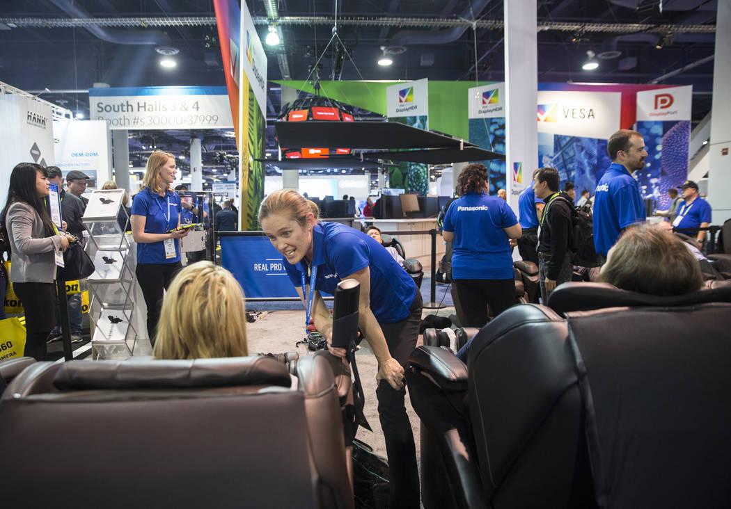 El expositor Stevyn Guinnip, en medio, guía a los asistentes a la convención a través de los beneficios del sillón de masaje Panasonic Real Pro Ultra durante el primer día del CES 2019 el mar ...