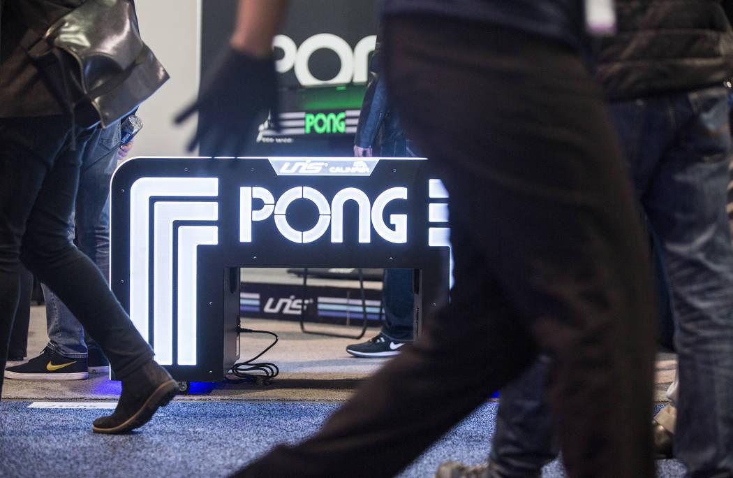 Los asistentes a la convención pasan la señalización para Pong durante el primer día del CES 2019 el martes 8 de enero de 2019, en el Centro de Convenciones de Las Vegas, en Las Vegas. El even ...