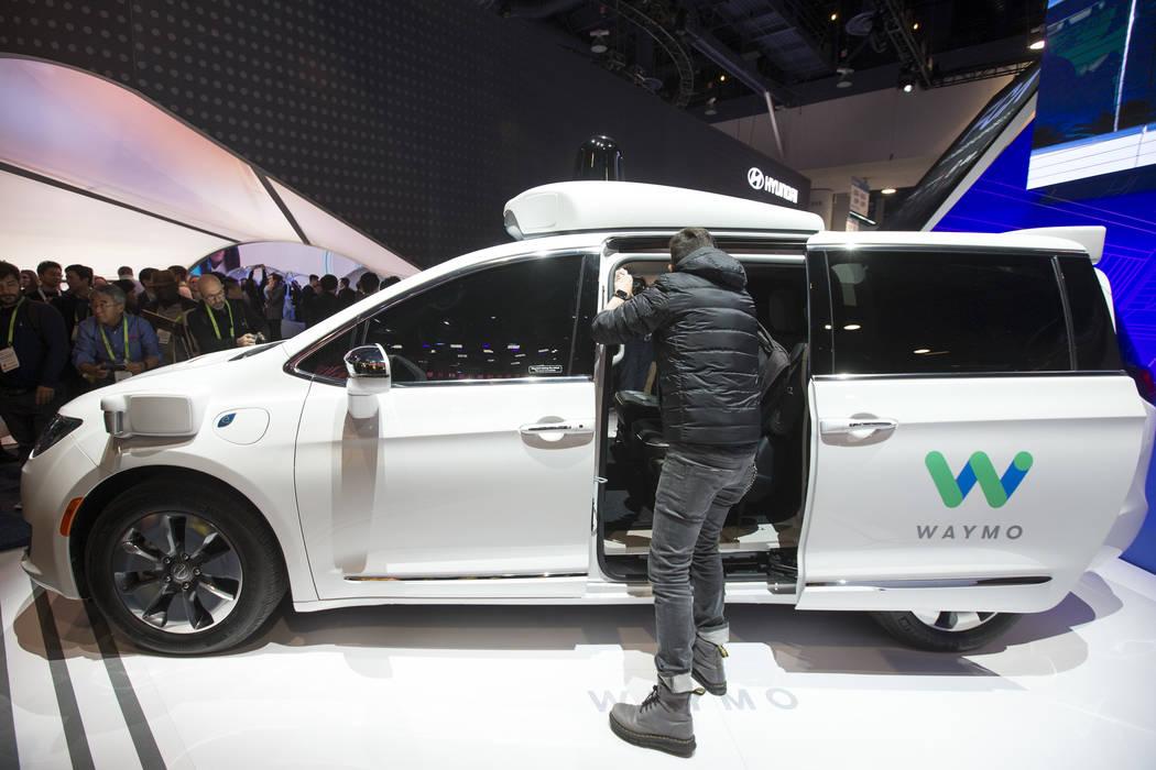 Los asistentes inspeccionan un auto de conducción de Waymo, la compañía hermana de Google, en exhibición en el stand de Fiat Chrysler Automobiles el primer día del CES en el Centro de Convenc ...