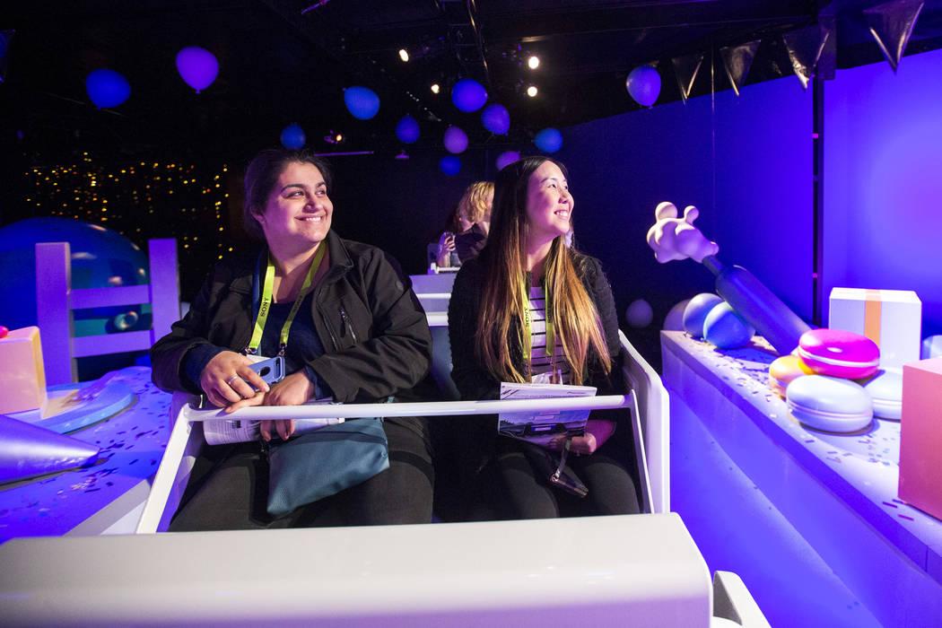 Los asistentes Azin Biatani, a la izquierda, y Sabrina Nguyen, con Fullerton College en California, dan una vuelta en un viaje de diversión promocionando al Asistente de Google, el asistente virt ...