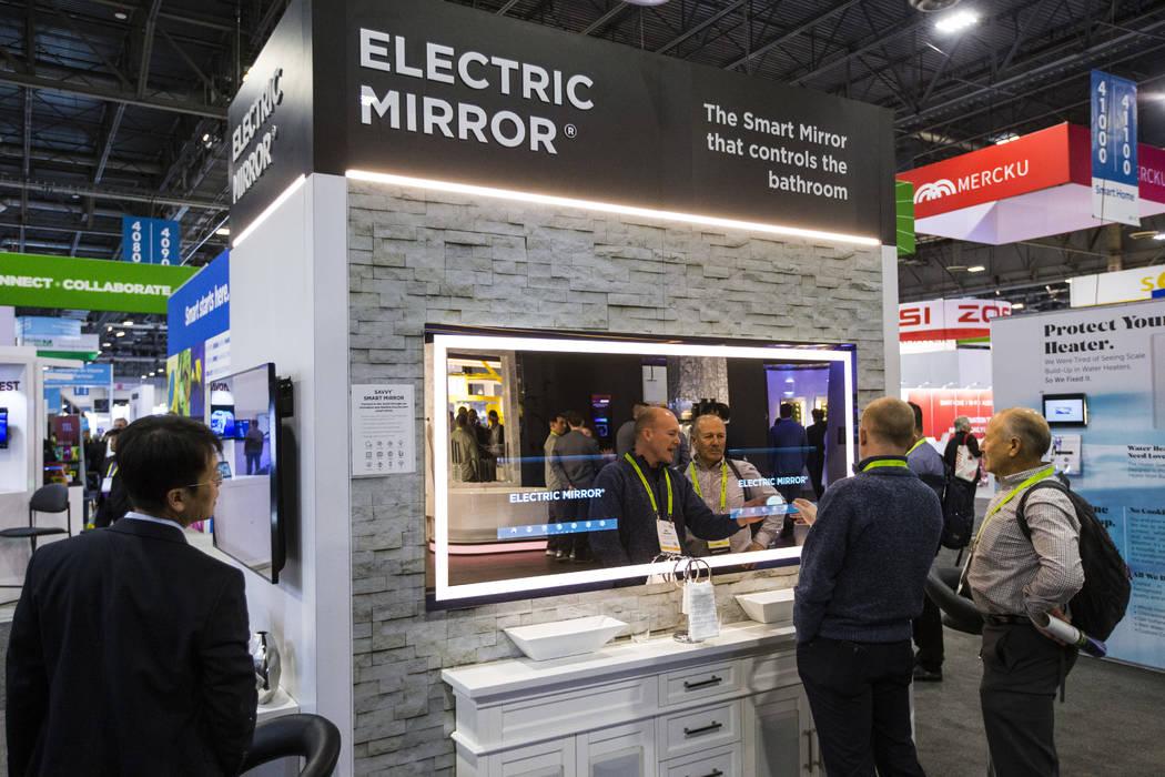 Jim Mischel, centro, y Gordon van Zuiden, a la derecha, miran un espejo eléctrico, con controles y una pantalla incorporada en una pantalla de espejo, el Sands Expo and Convention Center durante ...