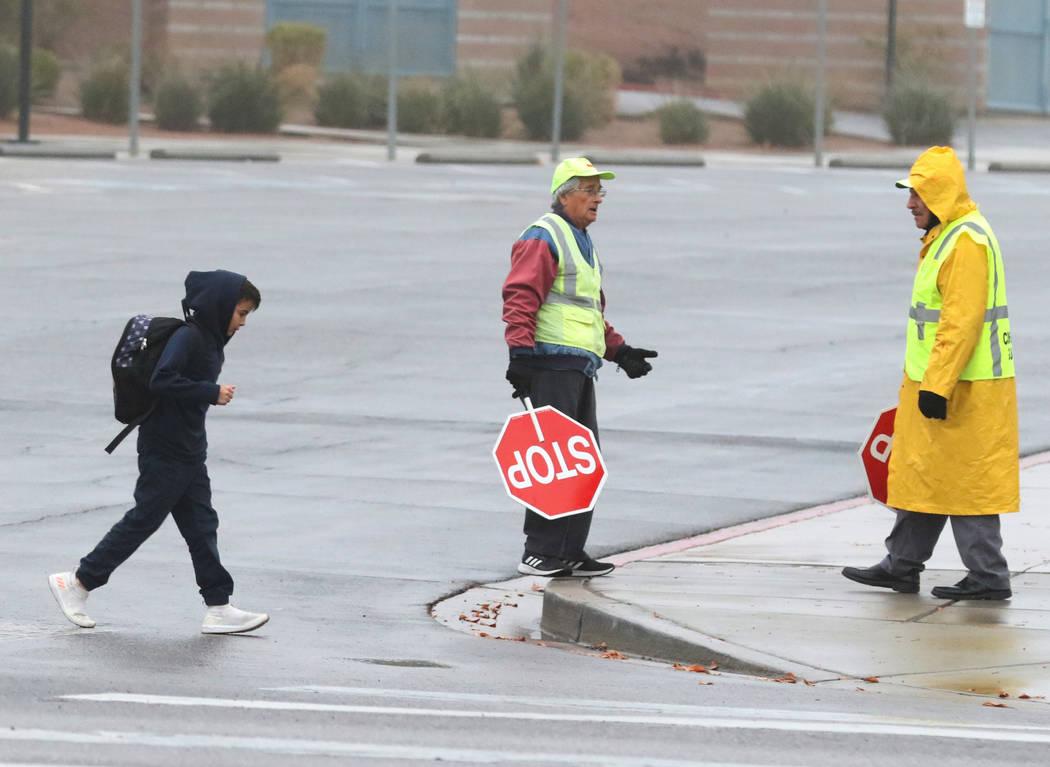 Un estudiante cruza Green Valley Parkway mientras los guardias de los cruces escolares observan el clima lluvioso el martes, 15 de enero de 2019, en Henderson. Bizuayehu Tesfaye / Las Vegas Review ...