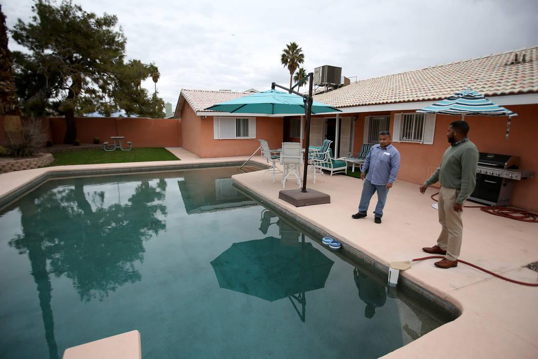"""El potencial comprador Tony Redding de Las Vegas, a la derecha, habla con la corredora Shannon Smith en la antigua casa del mafioso de Las Vegas Tony """"The Ant"""" Spilotro en 4675 Balfour Drive en La ..."""