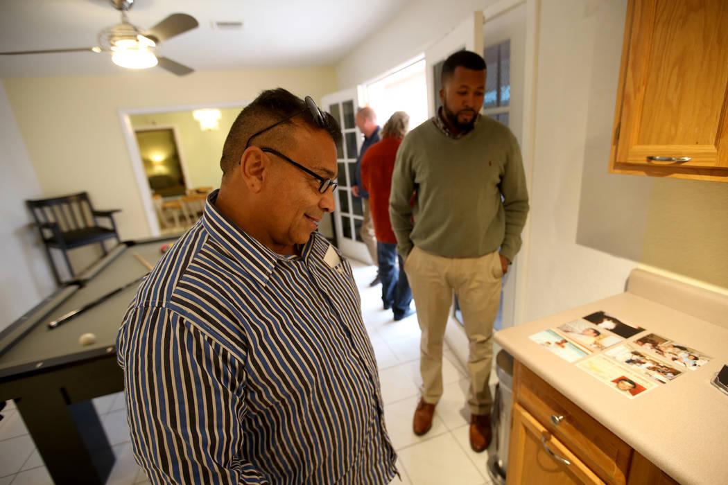 """El potencial comprador Tony Redding de Las Vegas, a la izquierda, mira las fotos históricas con la agente Shannon Smith en la antigua casa del mafioso de Las Vegas Tony """"The Ant"""" Spilotro en 4675 ..."""