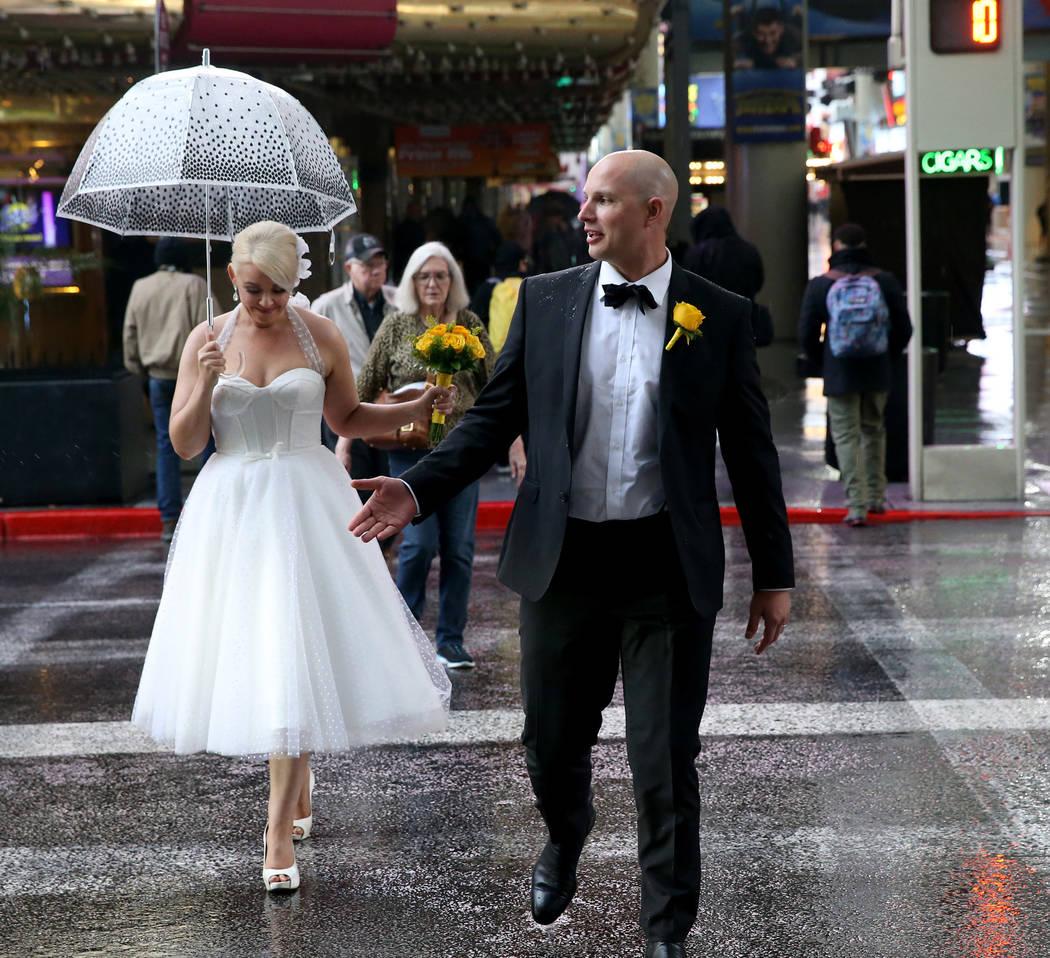 Kenda y Marcus Fox, recién casados, caminan a través de Casino Center Drive a través de una ligera lluvia en Fremont Street Experience en el centro de Las Vegas el martes 15 de enero de 2019. K ...