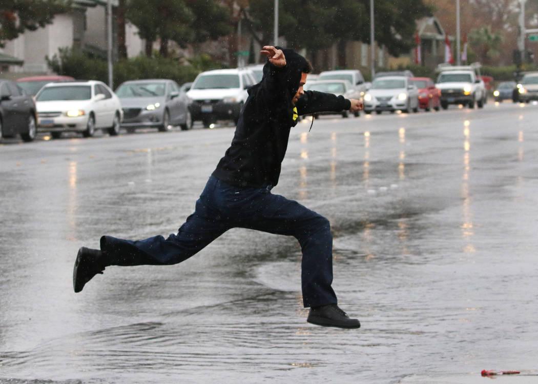 Un peatón salta sobre una calle inundada en la intersección de Eastern Avenue y Sahara Avenue el martes 15 de enero de 2019, en Las Vegas. Bizuayehu Tesfaye / Las Vegas Review-Journal @bizutesfaye