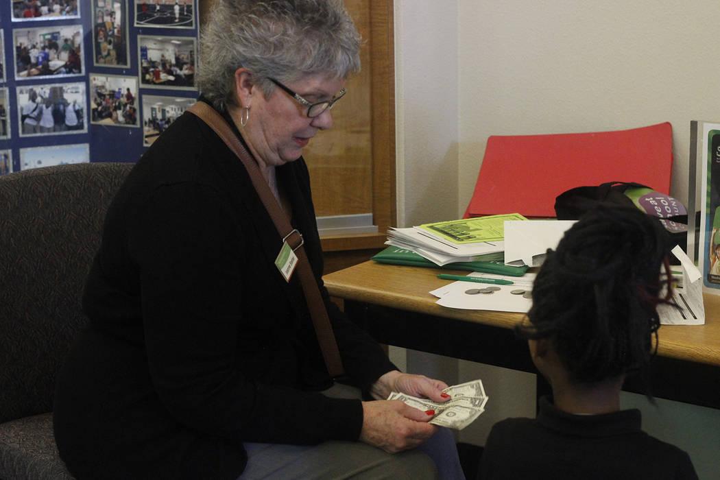 Joanne Stetler, banquera de la sucursal de Aliante de Washington Federal, recibe dinero de un estudiante de la escuela primaria Scott. (Mia Sims / Las Vegas Review-Journal @miasims___)