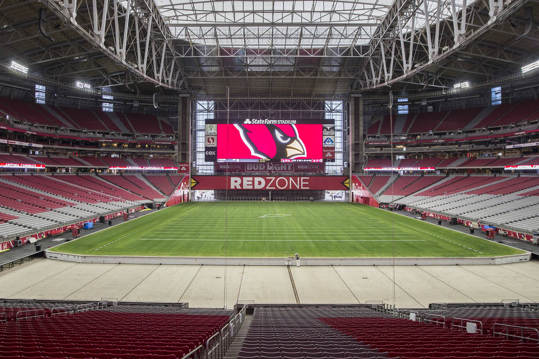 El ingeniero Don Kramer, en medio, supervisa la instalación del sistema de bandejas de césped en preparación para el juego de fútbol americano Phoenix Cardinals NFL en el estadio State Farm el ...