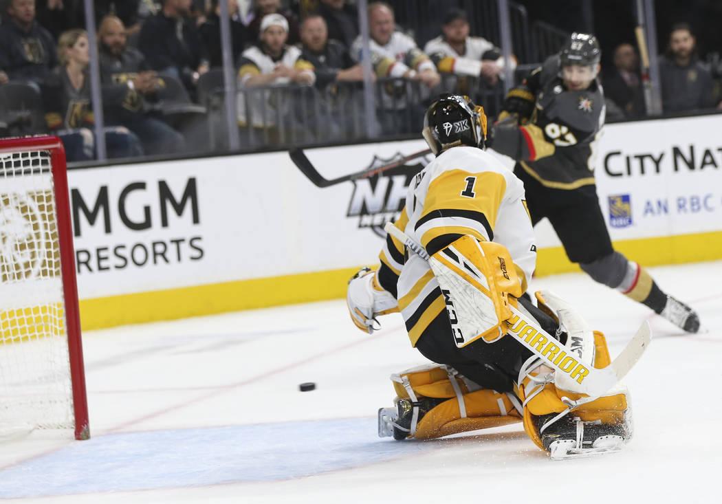 El portero Casey DeSmith (1) de los Pittsburgh Penguins entrega un gol al ala izquierda de los Caballeros Dorados, Max Pacioretty, fondo derecho, durante el primer período de un juego de hockey d ...