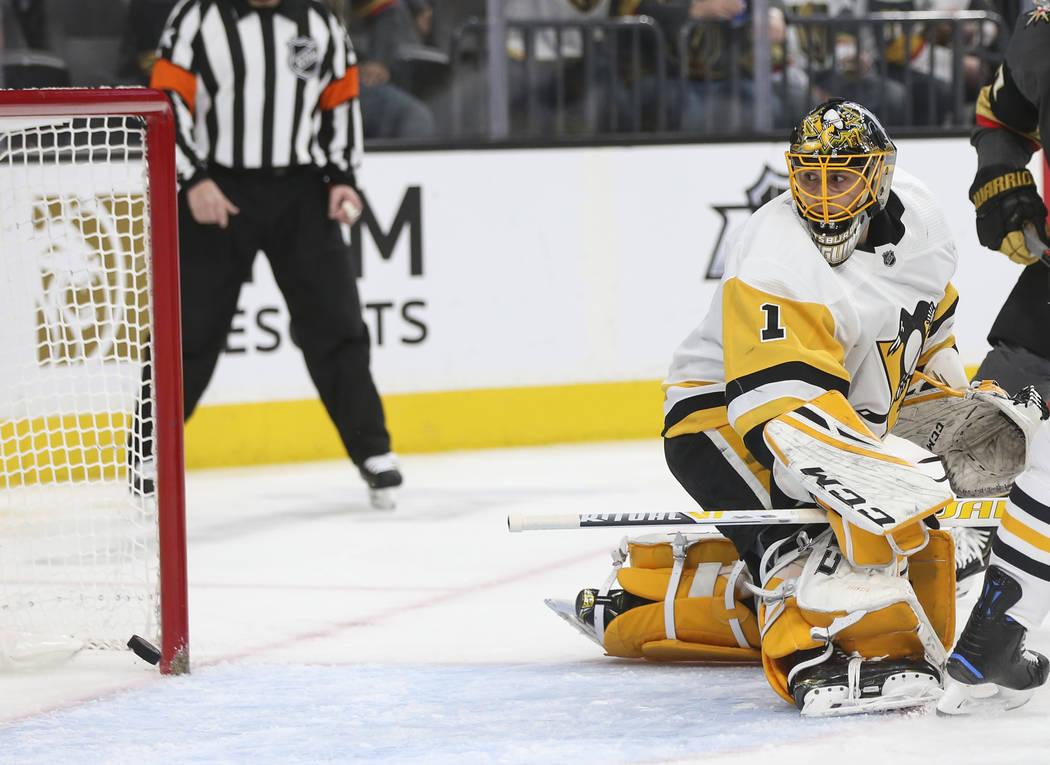 El defensa de los Golden Knights, Shea Theodore, que no aparece en la foto, anota un gol pasando al portero de los Pittsburgh Penguins, Casey DeSmith (1) durante el primer período de un juego de ...