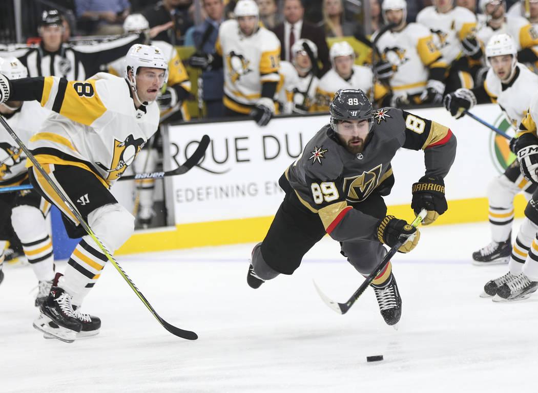 El ala derecha de los Golden Knights, Alex Tuch (89), se resbala mientras pasa el disco por el defensa Brian Dumoulin (8) de los Pittsburgh Penguins durante el primer período de un juego de hocke ...