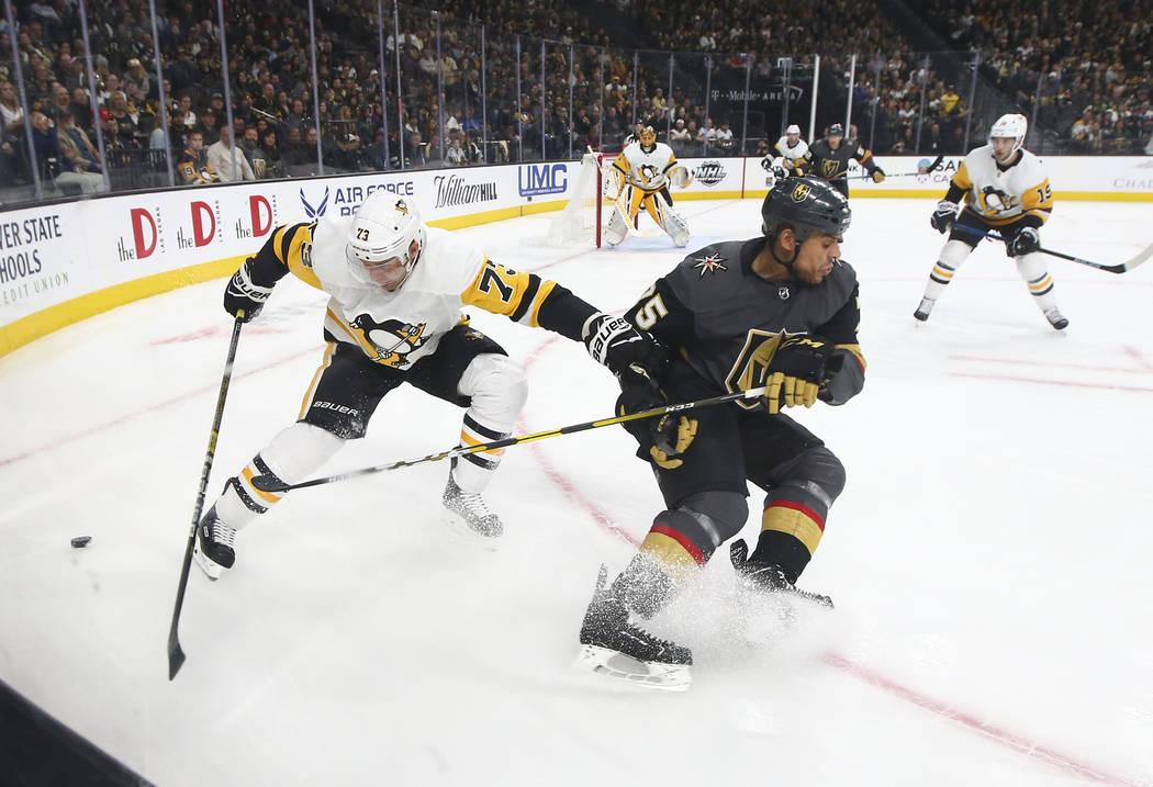El ala derecha de los Caballeros Dorados, Ryan Reaves (75), pelea por el disco contra el defensa de los Pittsburgh Penguins, Jack Johnson (73), durante el primer período de un juego de hockey de ...