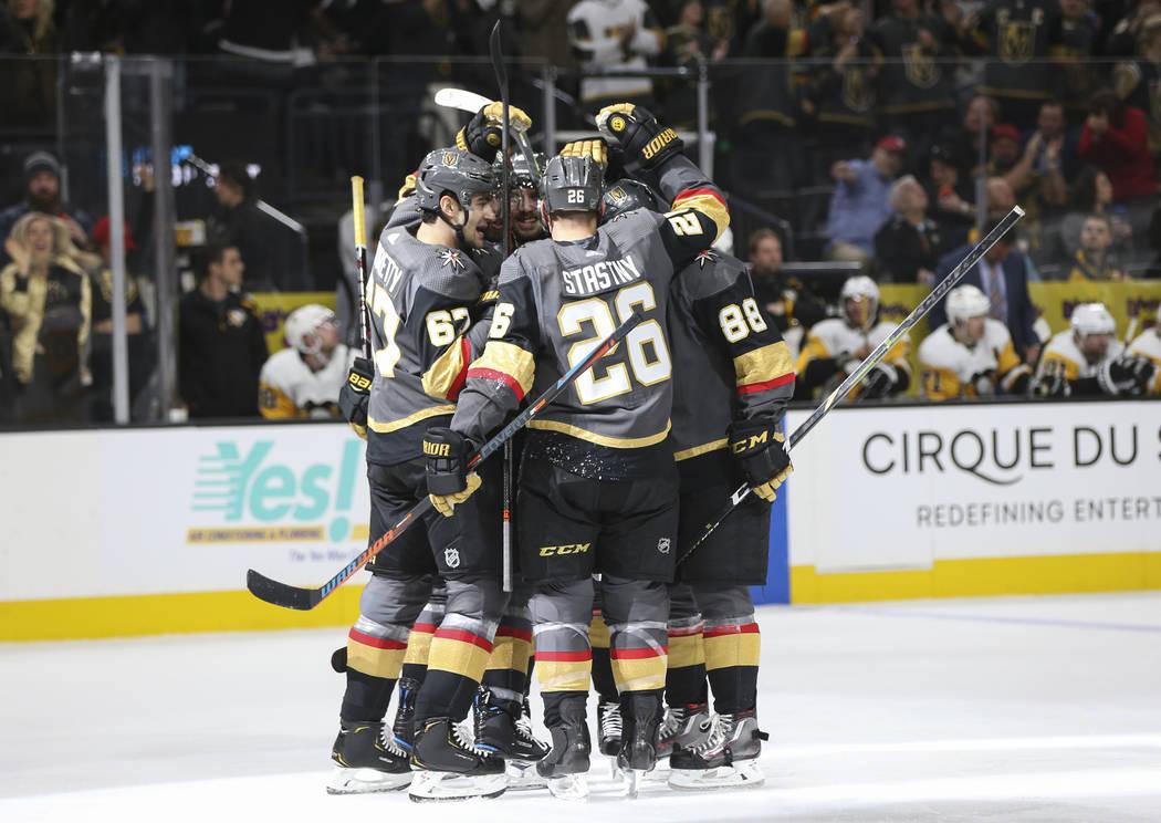 Los jugadores de los Golden Knights celebran un gol del defensa Shea Theodore durante el primer período de un juego de hockey de la NHL contra los Pittsburgh Penguins en el T-Mobile Arena de Las ...
