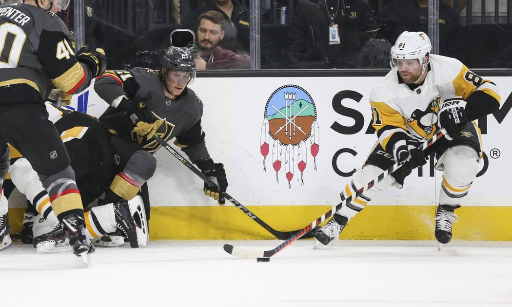 El ala derecha de los Pittsburgh Penguins, Phil Kessel (81), mueve el disco al centro de Cody Eakin (21) de los Golden Knights durante el primer período de un juego de hockey de la NHL en T-Mobil ...