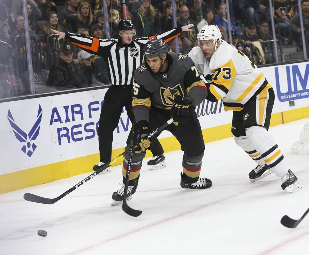 El ala derecha de los Caballeros Dorados, Ryan Reaves (75) y el defensa de los Pittsburgh Penguins, Jack Johnson (73), luchan por el disco durante el primer período de un juego de hockey de la NH ...